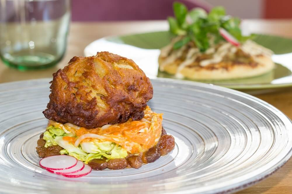 Onion bhaji with coronation slaw, tomiolli, lettuce